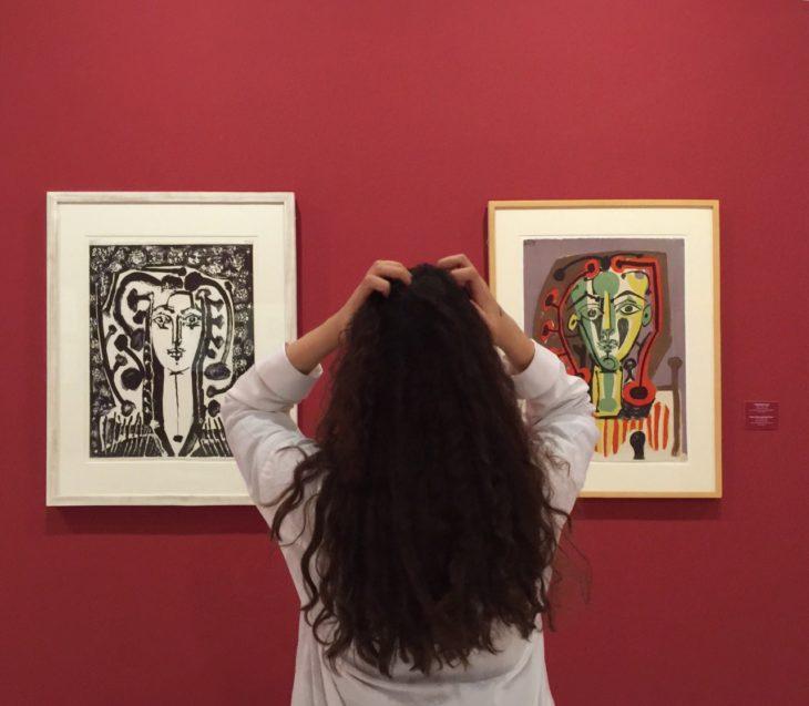 Chica de cabello rizado y largo mira cuadros en un museo con pared roja