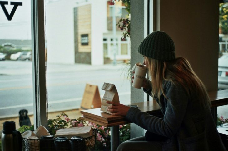 Chica rubia toma café mientras por la ventana de una caftería