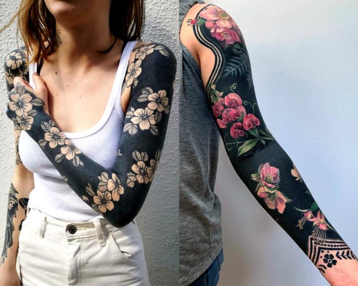 Estilos de tatuajes femeninos; blackout, tatuaje de flores en fondo negro en el brazo; full sleeve