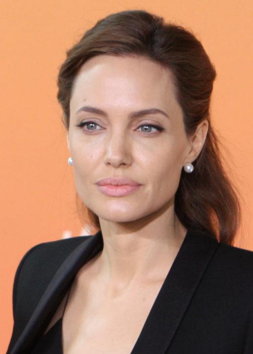 Angelina Jolie posando en una alfombra naranja