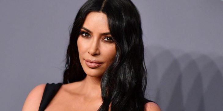 Kim Kardashian sonriendo ligeramente posando en una alfombra gris