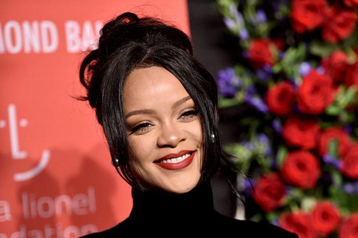 Rihanna sonriendo ligeramente e una alfombra roja son rosas