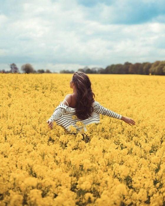 Mujer con los brazos extendidos en campo de flores