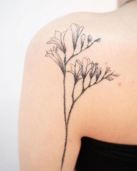 Tatuaje al estilo hand poke de flores y botones de flores abriéndose en el área del omóplato