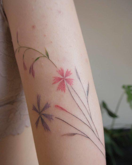 Tatuaje al estilo hand poke de flores de colores en el área del brazo