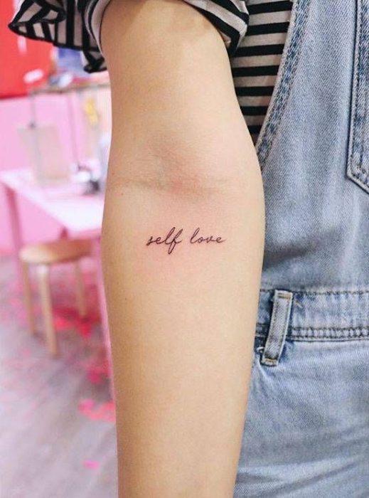 Tatuaje de frase en la zona interna del antebrazo