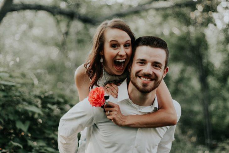 Chico cargando a su novia en la espalda