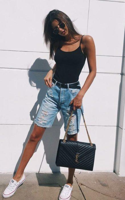 Chica usando bermudas de mezclilla con un top de color negro