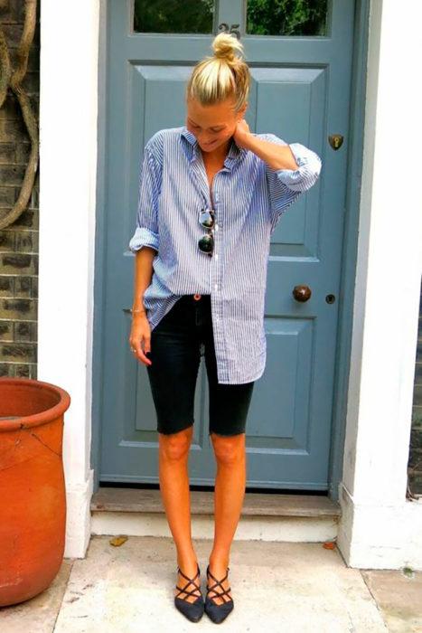 Chica usando bermudas de color negro con blusa de color azul semi fajada