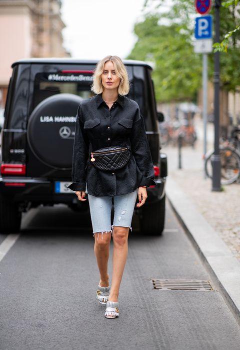 Chica usando bermudas de mezclilla con blusa larga de color negro y cangurera