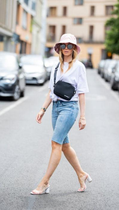 Chica usando bermudas de mezclilla con blusa de color blanco