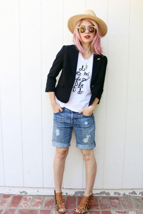 Chica usando bermudas de mezclilla con playera de color blanco con un blazer de color negro