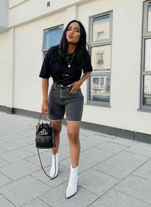 Chica usando bermudas de mezclilla con blusa de color negro y botines blancos