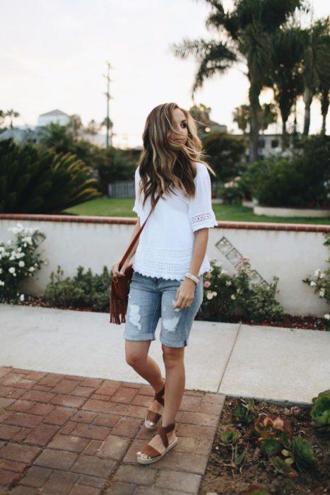 Chica usando bermudas de mezclilla con blusa de color blanco y sandalias