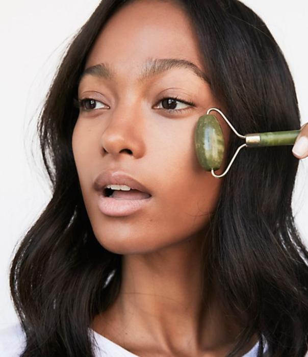 Mujer utilizando el rodillo de jade sobre su rostro