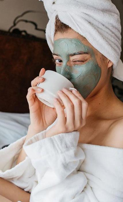 Mujer con mascarilla verde en el rostro, mientras toma un té relajada