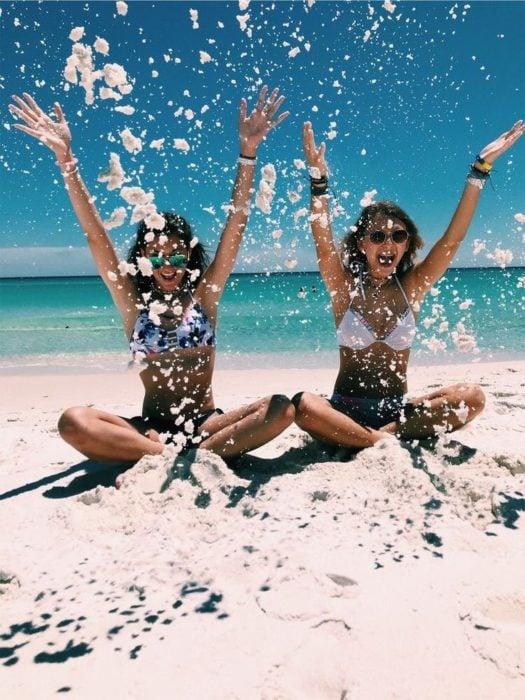 Chicas sentadas en la playa a la orilla del mar