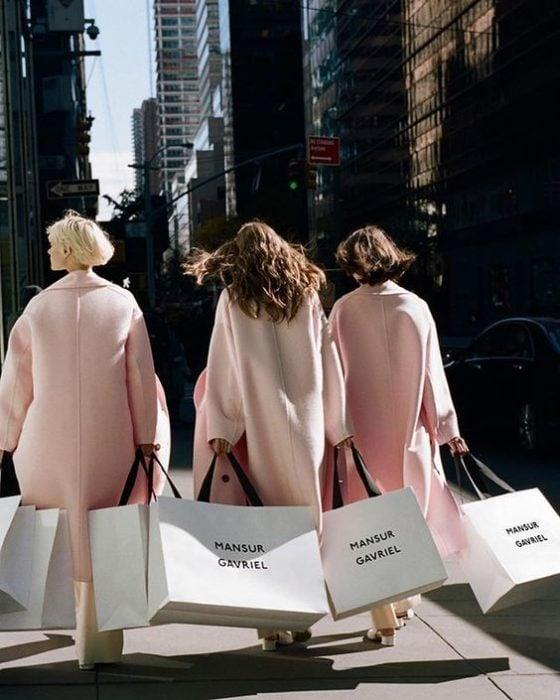 Grupo de amigas saliendo de comprar con sacos rosas pastel