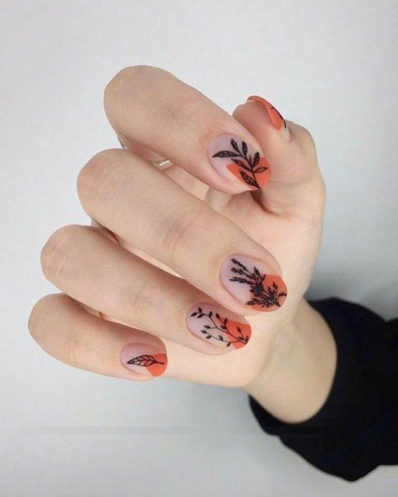 Manicura de estilo francés con flores en tonos negros con naranja