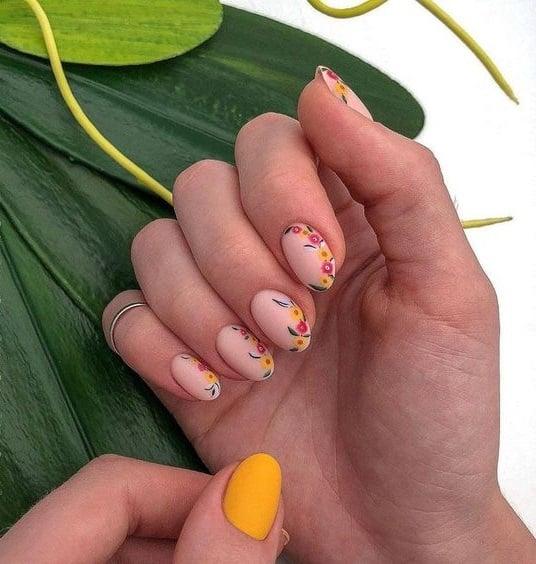 Manicura estilo francés con flores en tonos naranja, amarillo y verde