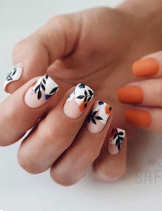 Manicura estilo francés con flores naranjas con fondo blanco y guias verdes