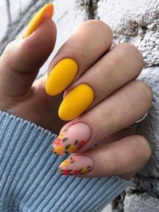 Manicura estilo francés con flores en dos uñas y en contraste con amarillo y naranja en guias verdes