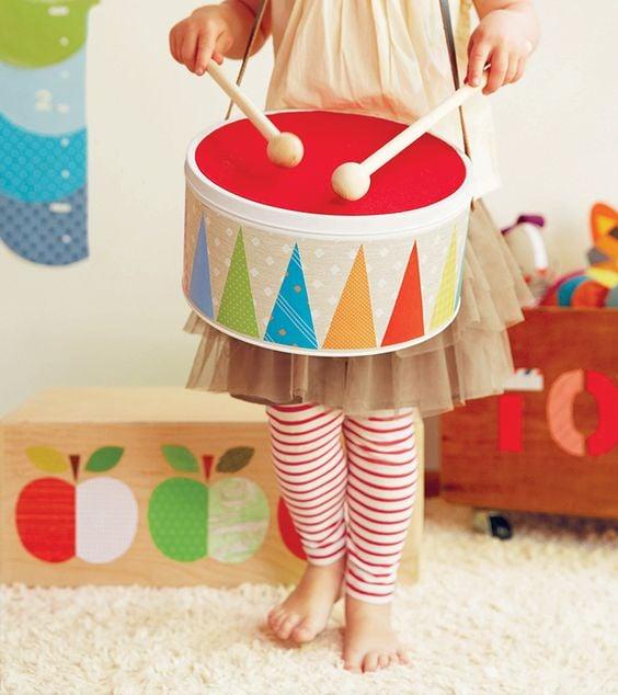 Niña jugando con un tambor de colores
