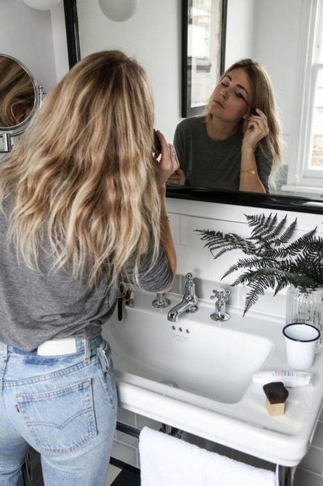 Chica maquillándose frente al espejo