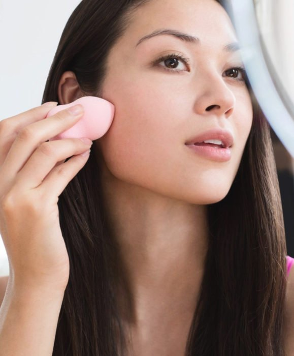 Maquillaje para labios con Labello Scrubs; mujer aplicando base líquida con esponja frente al espejo