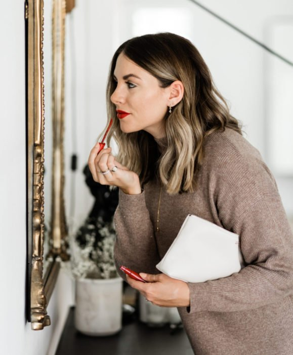 Maquillaje para labios con Labello Scrubs; mujer aplicando labial frente al espejo
