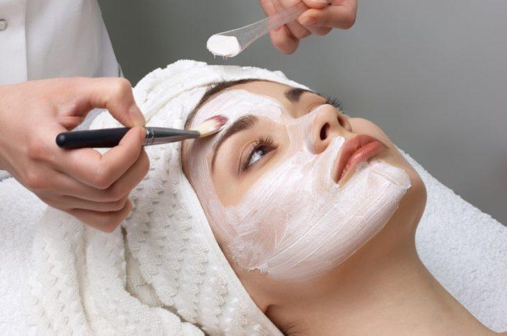 Mujer en un spa a la que le aplican una mascarilla