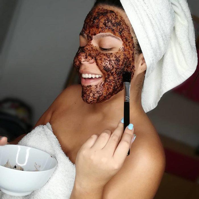 Chica aplicando una mascarilla facial de café