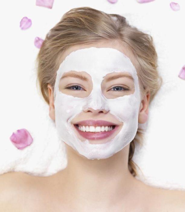 Chica sonriendo mientras tiene aplicada una mascarilla en el rostro