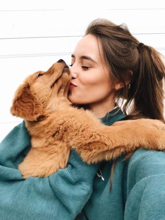 Chica abrazando y besando a su perrito