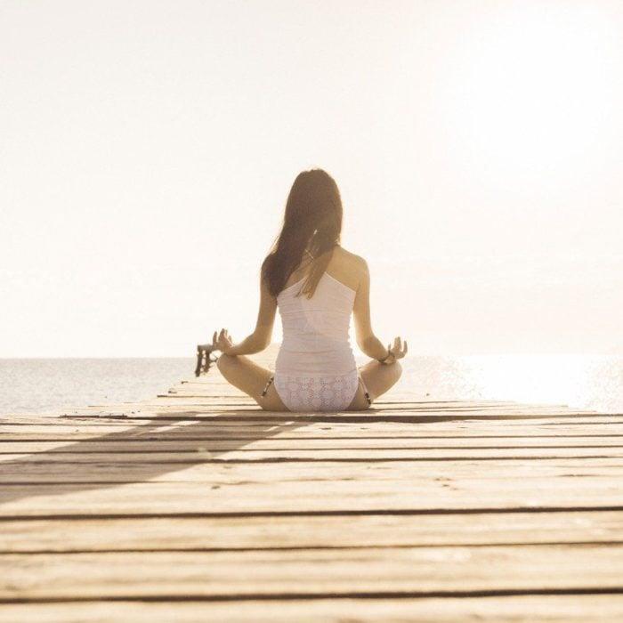 Chica meditando en un muelle