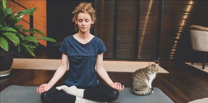 Chica meditando en casa en compañía de su gato