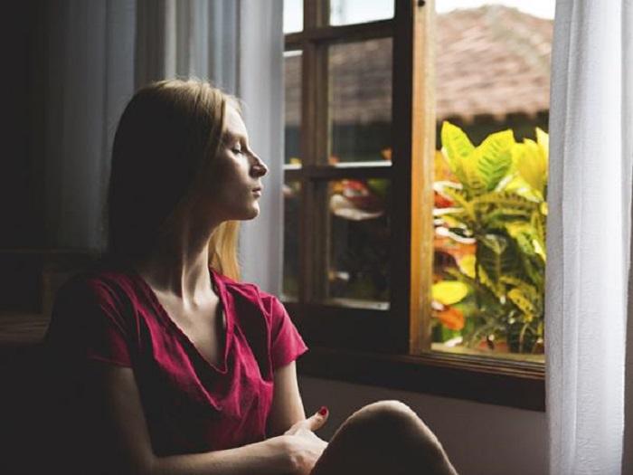 Chica meditando cerca de la ventana