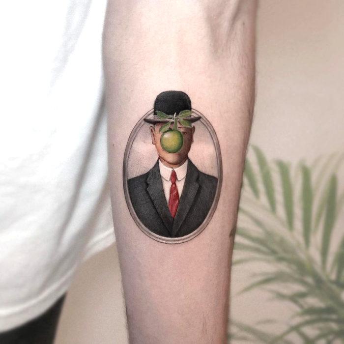 Minitatuajes realistas de Eden Kozokaro; El hijo del hombre por Rene Magritte