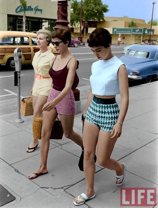 Moda femenina de los 70; amigas caminando en la calle, short de cuadros rosa y negro, de rombos azules y verdes, ropa retro; corte de cabello pixie