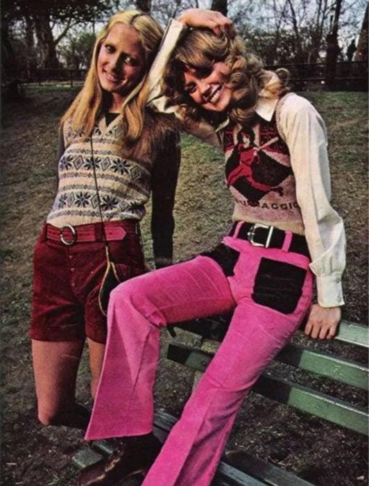 Moda femenina de los 70; amigas sentadas en la banca del parque, suéter de rombos tejido, short de pana rojo, pantalón rosa con negro; peinados y ropa retro