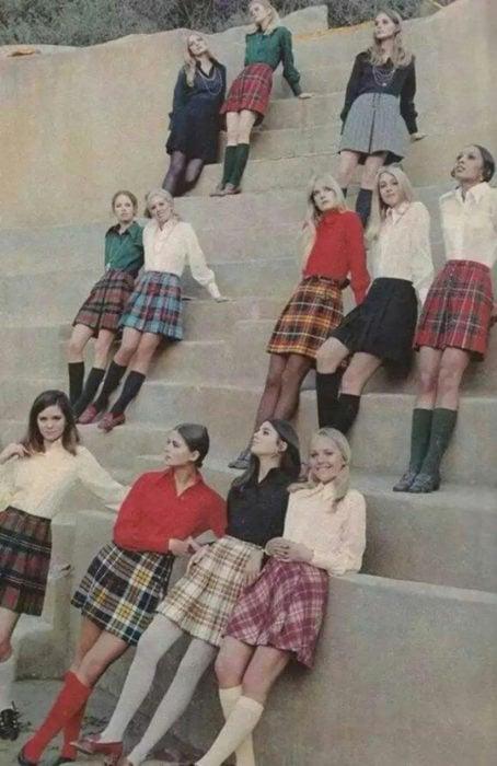 Moda femenina de los 70; grupo de mujeres sentadas en las escaleras con uniforme de estudiante; falda tableada de cuadros, blusas formales blancas, verdes, rojas y negras; ropa y peinados retro