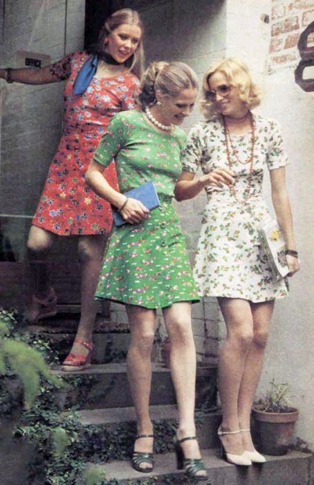 Moda femenina de los 70; amigas bajando escaleras, vestidos florales arriba de la rodilla, rojo, blanco y verde, con sandalias; ropa y peinados retro
