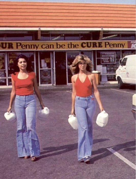 Moda femenina de los 70; mujeres amigas en estacionamiento saliendo de la tienda, con jeans acampanados y blusa roja; ropa y peinados retro
