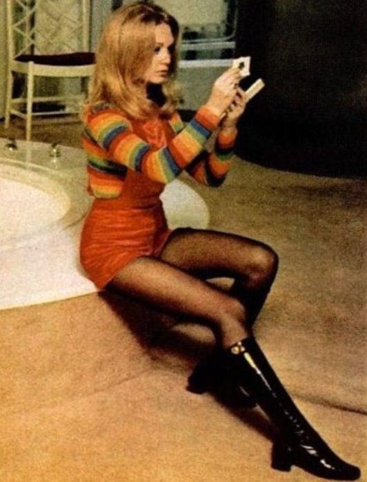 Moda femenina de los 70; mujer sentada mirándose en un espejo de mano, con overol rojo, blusa de manga larga de arcoíris, medias negras y botas a la rodilla; peinado y ropa retro