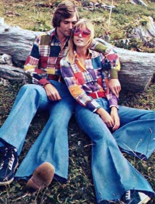 Moda femenina de los 70; pareja sentada en un tronco al aire libre, camisa de retazos de tela, jeans azules acampanados y tenis negros con blanco; ropa retro