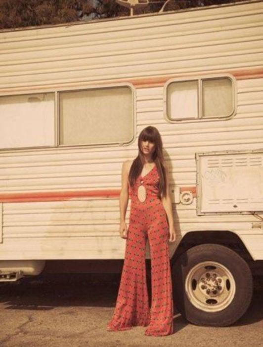 Moda femenina de los 70; mujer frente a un camper con onesie rojo acampanado de flores de escote al ombligo, cabello largo lacio y castaño; ropa retro