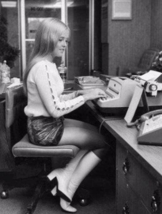 Moda femenina de los 70; mujer sentada en escritorio escribiendo en máquina de escribir, cabello rubio, lacio y largo, suéter de hoyos en las mangas, falda corta, botas largas y blancas; ropa retro