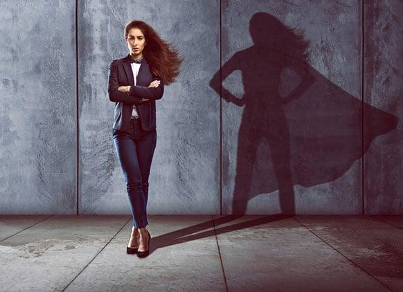 Mujer de pie con los brazos cruzados y como sombra una superheroina