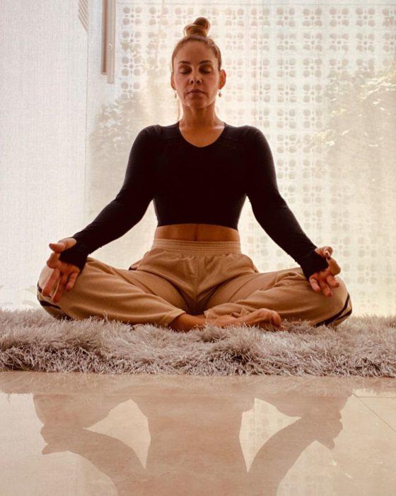 Mujer meditando en casa con ropa cómoda
