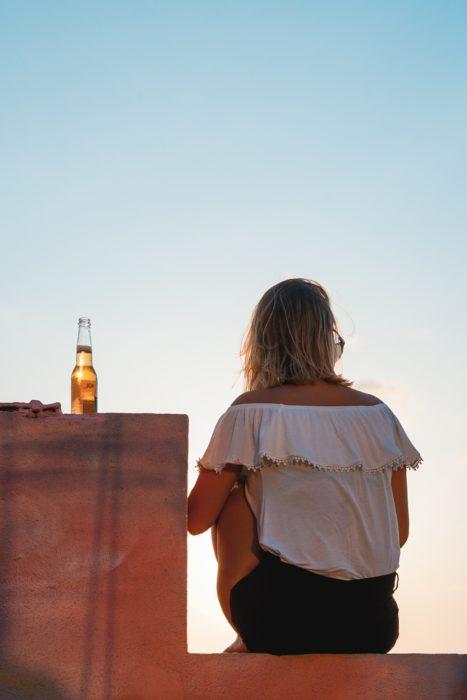 Chica sentada de espaldas y una cerveza en la barrita